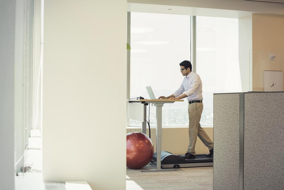 Businessman training on tread mill while using laptop