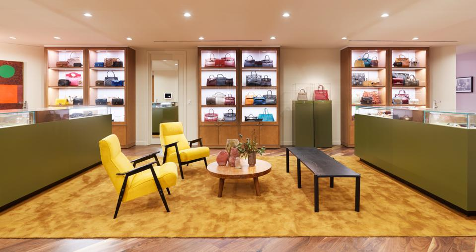 The handbag area of The RealReal's Chicago store has a residential feel with vintage yellow chairs surrounding a plant-filled coffee table.