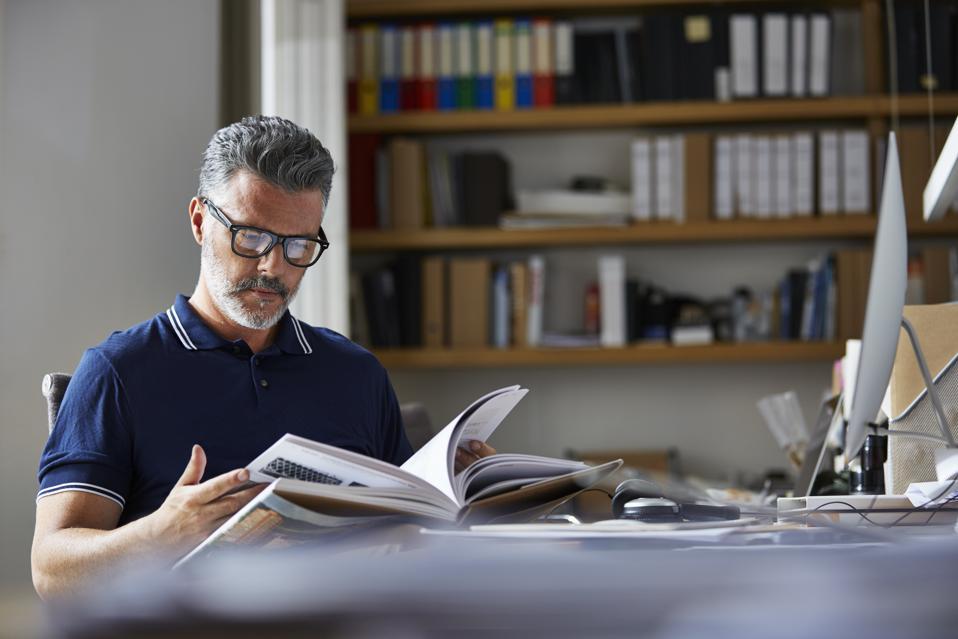 Businessman reading book at desk