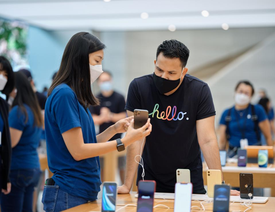 Apple retail employee showing a customer an iPhone 12. Both are wearing masks.