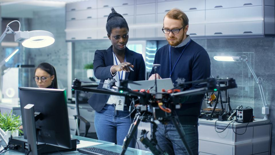 Caucasian Male and Black Female Engineers Working on a Drone Project with Help of Laptop and Taking Notes. He Works in a Bright Modern High-Tech Laboratory.