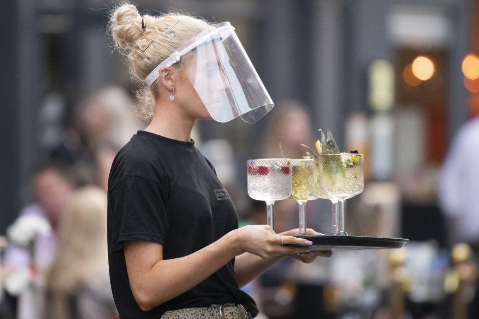 Waiter wearing a face shield without a mask.
