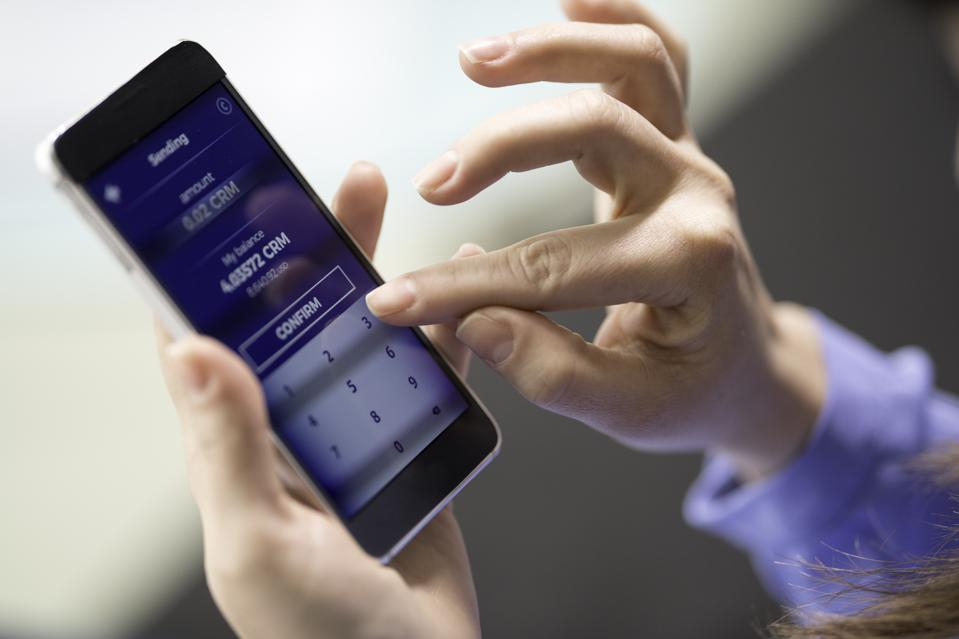 Woman sending cryptocurrency through a smart phone app