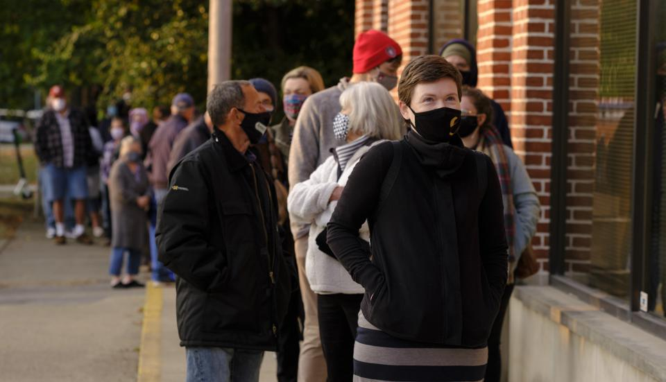Several voters wearing masks are seen lined up outside Bloomington, Indiana