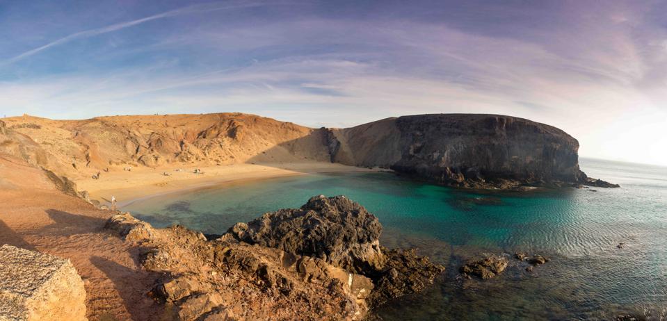 empty sandy beach, volcanic rock, green clear water