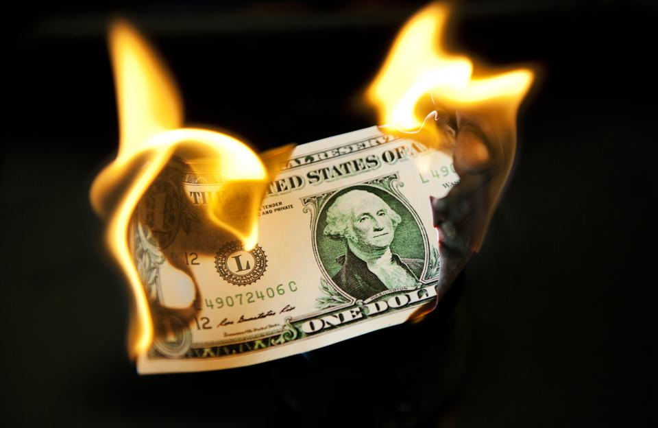 Dollar in flames to represent spending more than necessary on health insurance