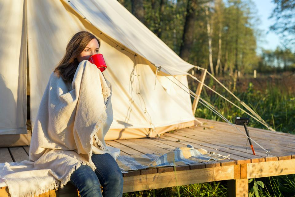 Young woman wraps blanket over herself while drinking coffee near canvas tent in the morning