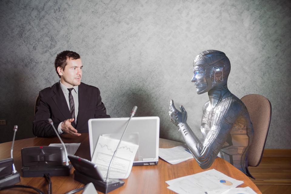 Man and a robot sitting in a conference room, and they are talking about work.