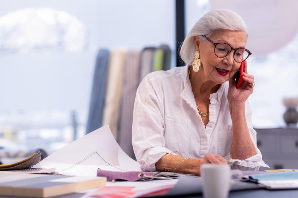 well-groomed older boss speaking on the phone in office.