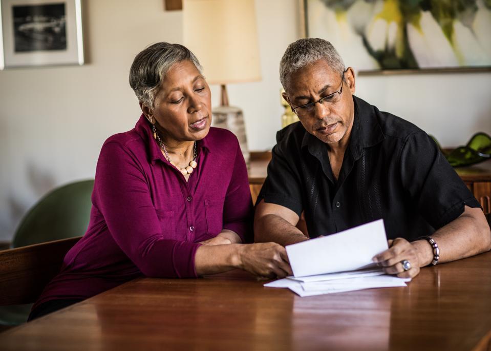 Senior couple (60yrs) paying bills at home