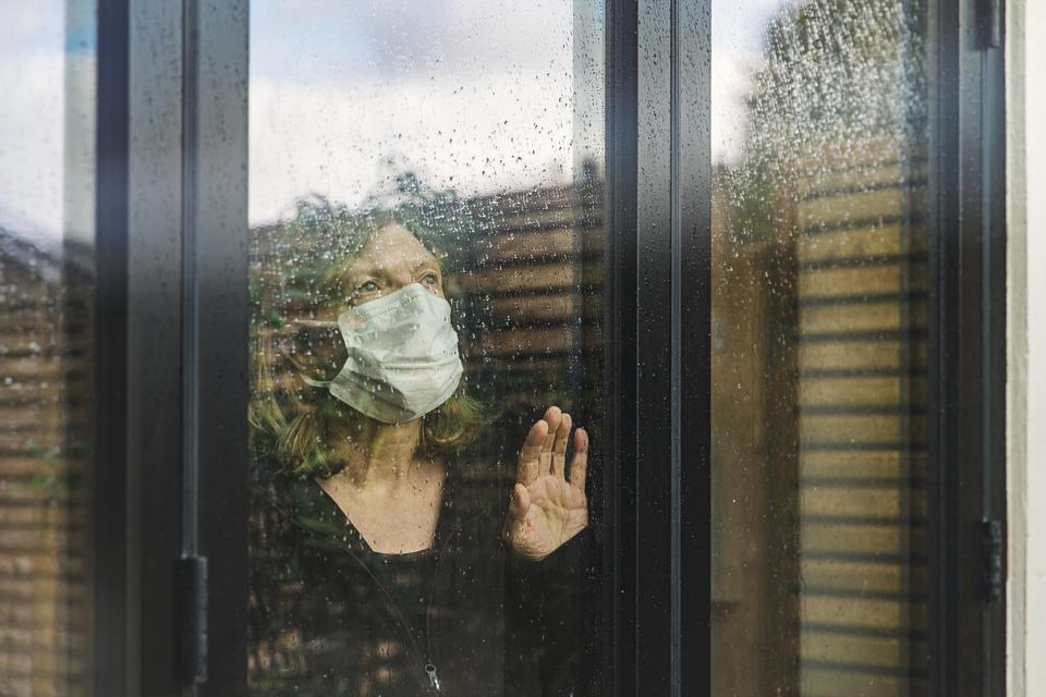 Office worker with mask looking through home office window