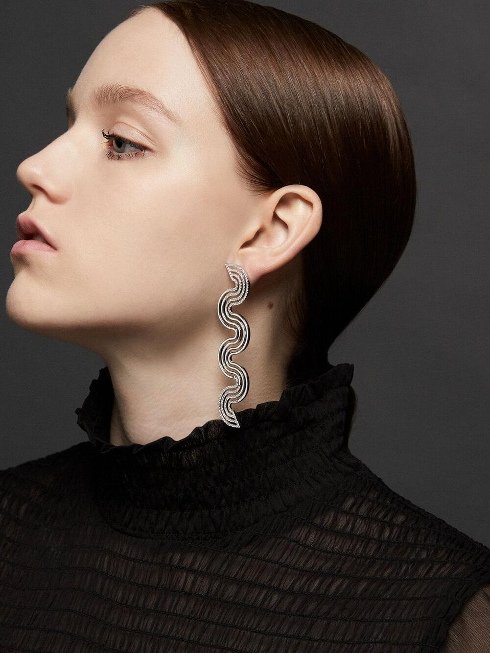 These dynamic, sculptural earrings feature black enamel and diamonds, which creates the effect of movement.