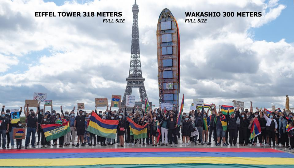 A superimposed image of the actual scaled image of the Wakashio compared to the Eiffel Tower by Mauritian-French photographer Eric Deniset.  Front of image shows French protestors on 29 August against the Wakashio oil spill.