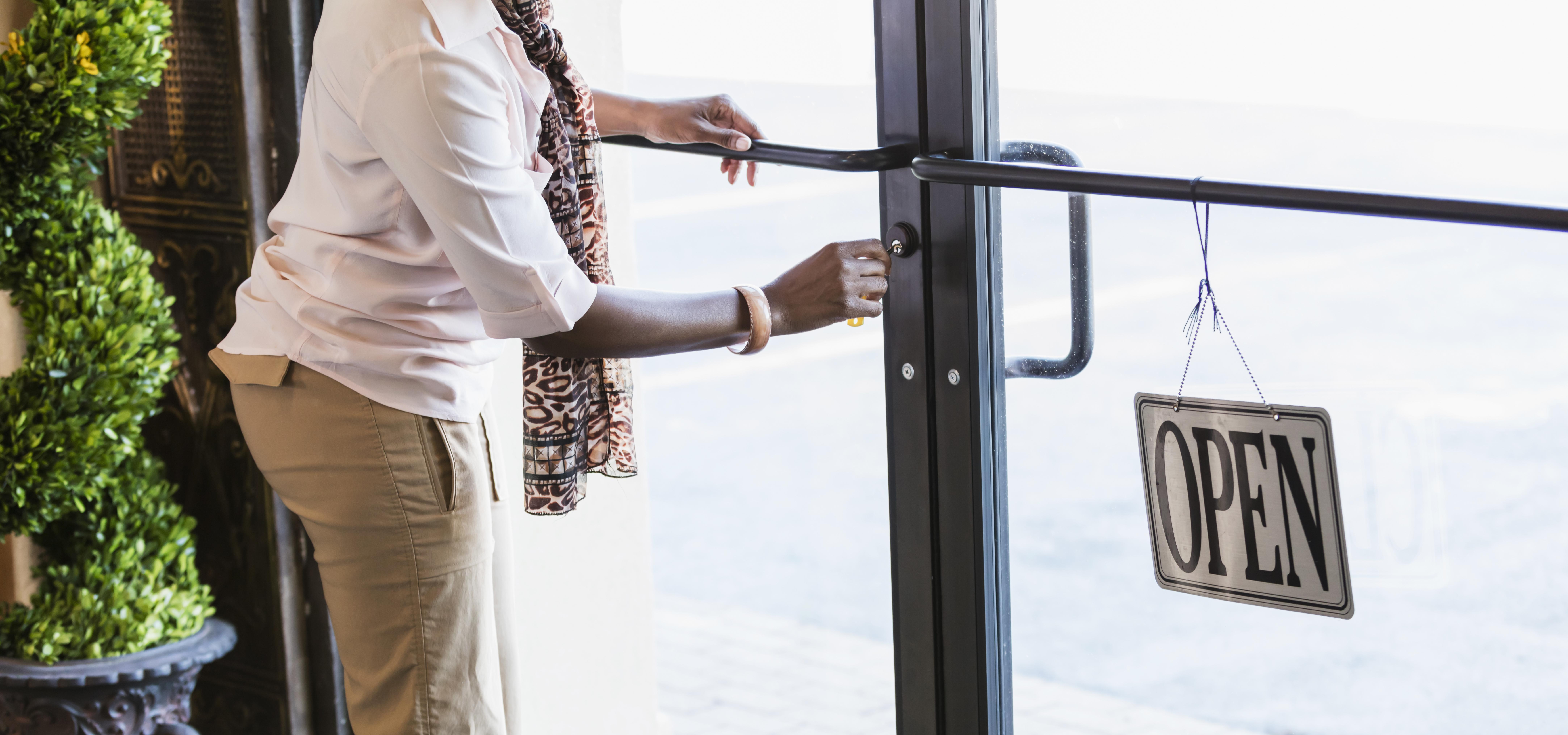 African-American woman opening store, unlocking the door
