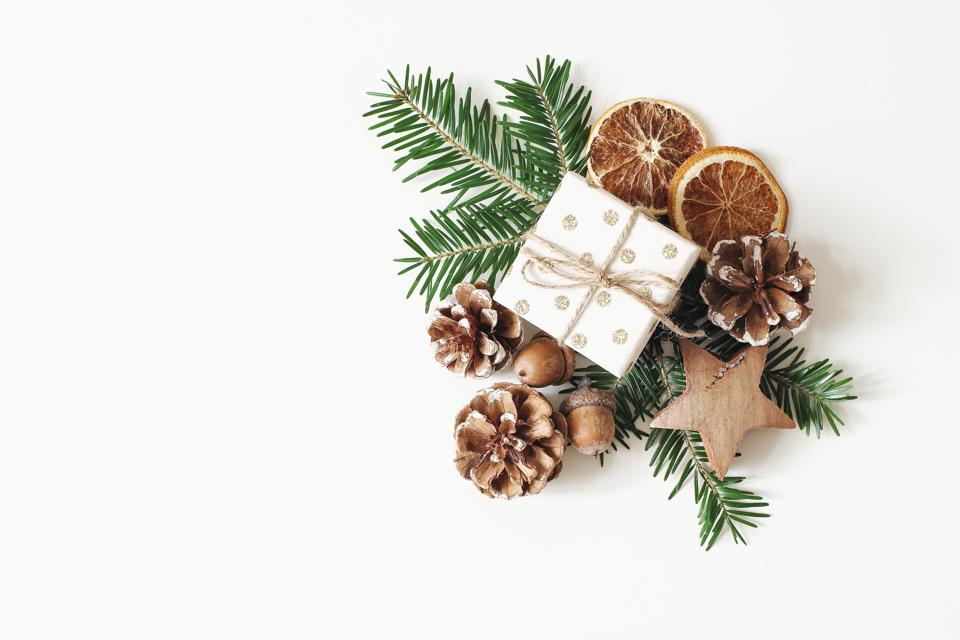 Christmas festive styled stock composition. Hand wrapped gift box, dry orange fruit slices, acorns, pine cones and fir tree branches isolated on white table background. Winter flat lay, top view.