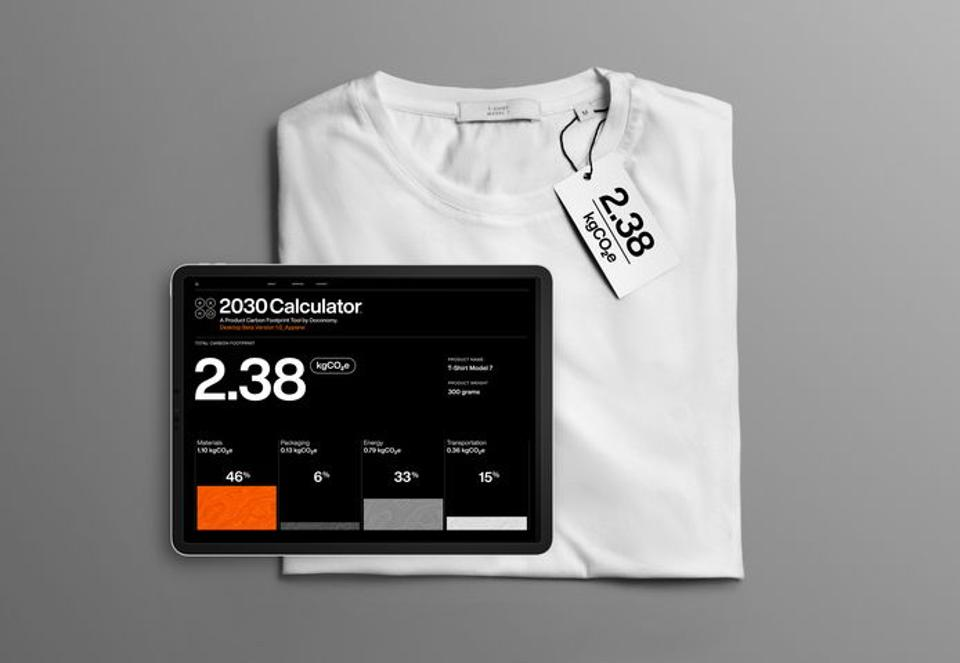A T-shirt displayed along with its carbon emissions impact on a tablet.
