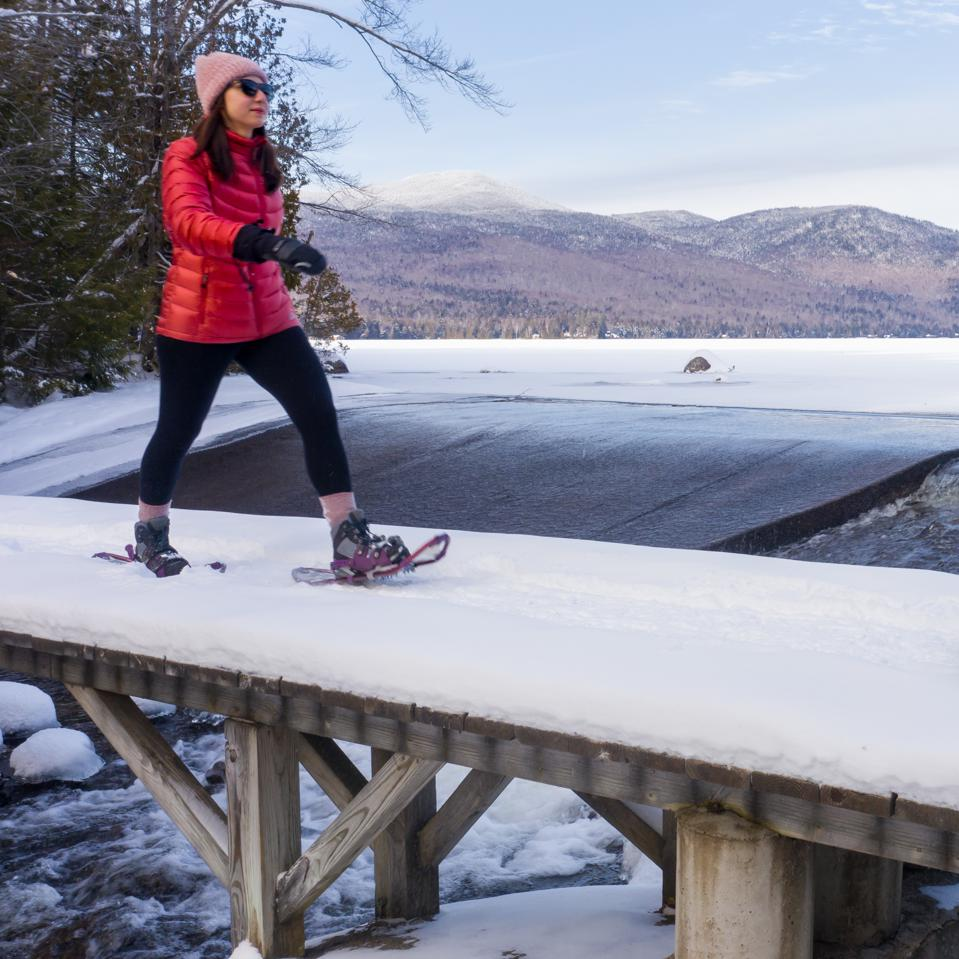 A woman snowshoeing at Lake Placid, New York.