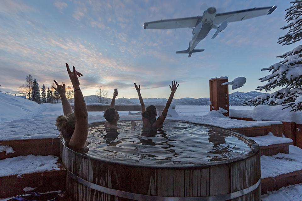 People in a hot tub waving to a plane in Alaska.