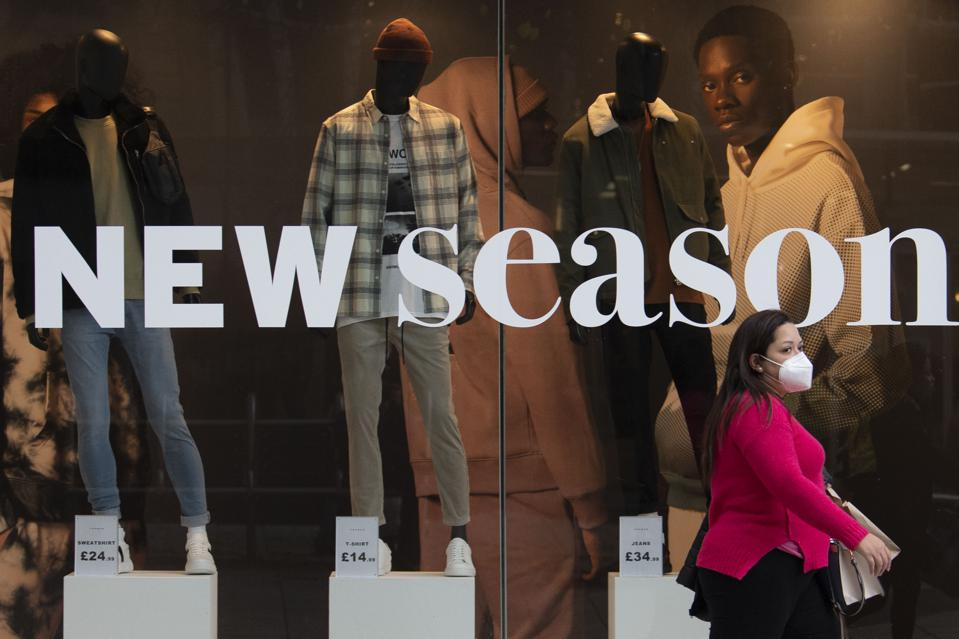A woman in a face mask walks past a high street fashion store display reading ″new season″