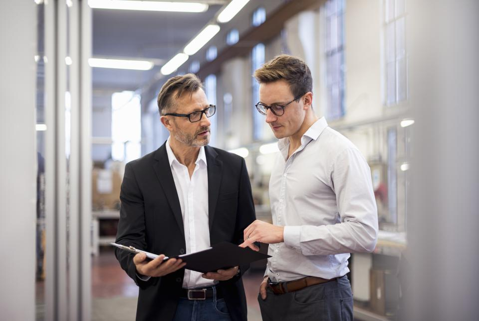 Two businessmen in factory looking at folder