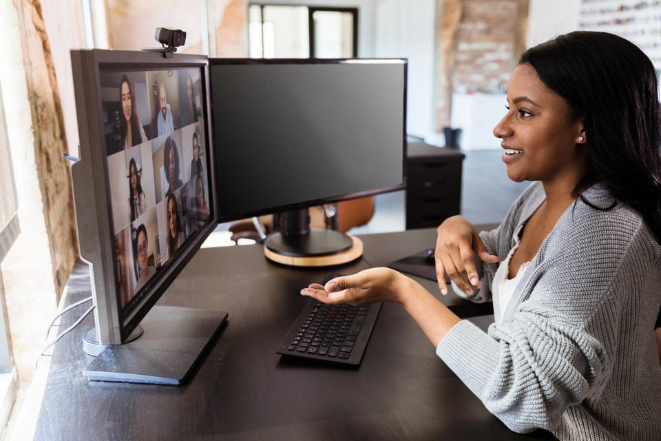Businesswoman talks with colleagues during virtual meeting
