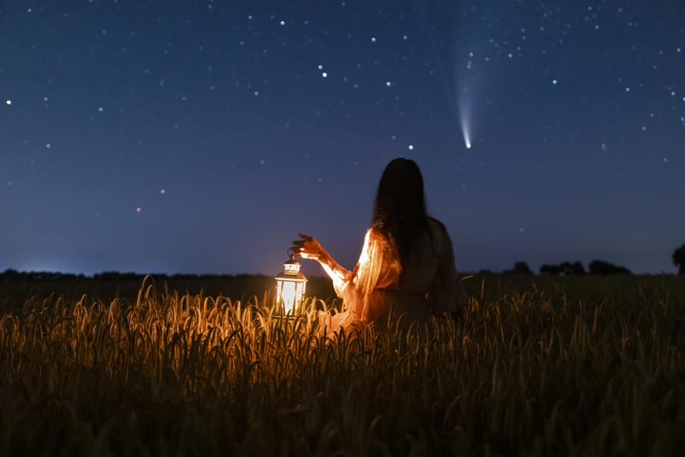 Woman in field with lantern on background of Comet Neowise C/2020 F3