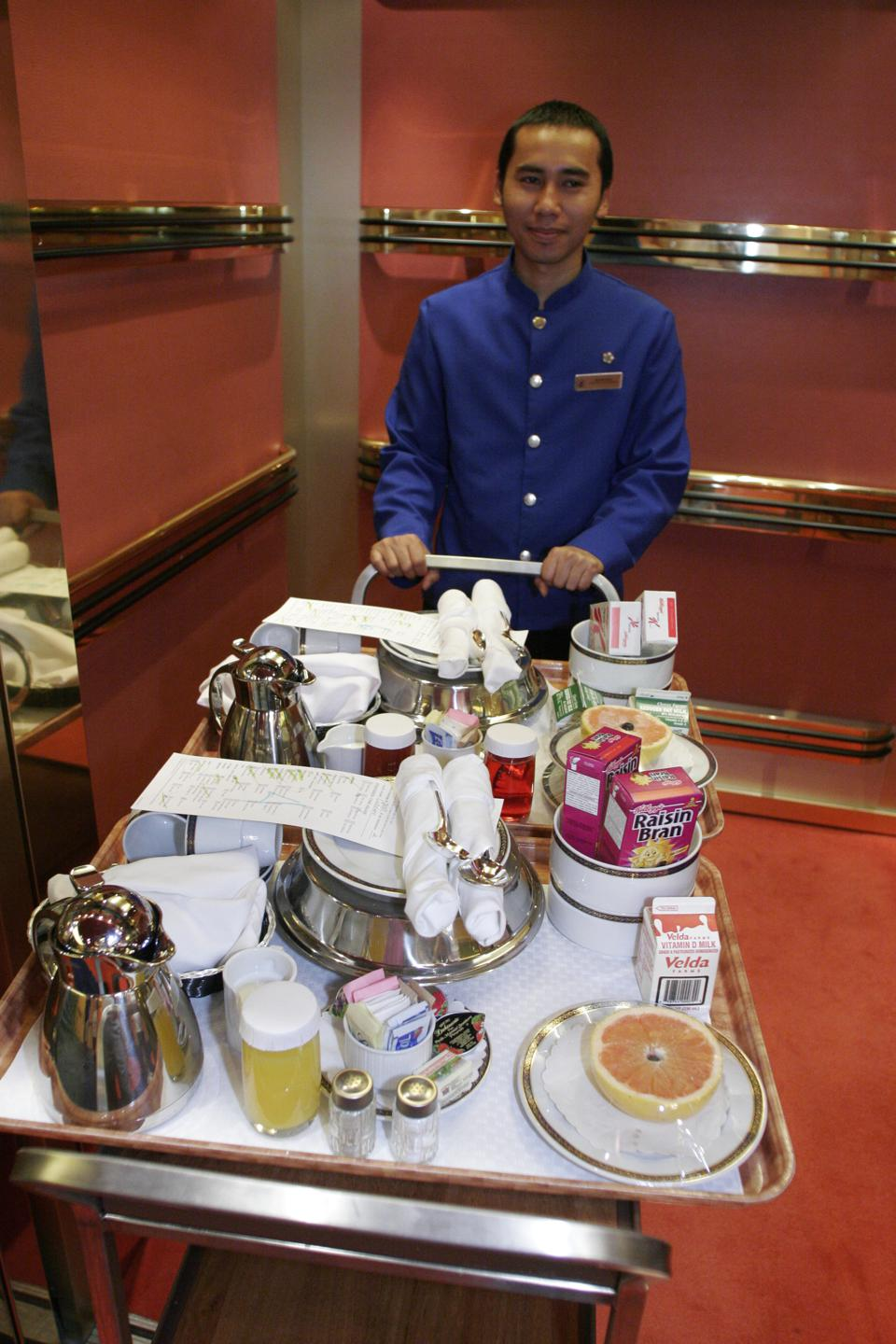 An Asian male with a food cart in the elevator on the mms Noordam.