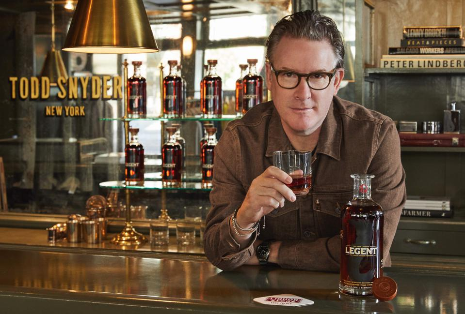 Designer Todd Snyder wears a whiskey-colored denim jacket with a glass of bourbon in hand