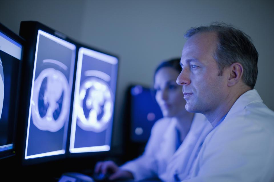 Doctors looking at MRI images on computer screens