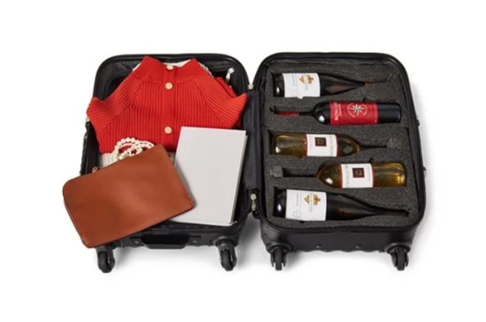 A suitcase is filled with garments, personal items, and five safely-padded bottles of wine