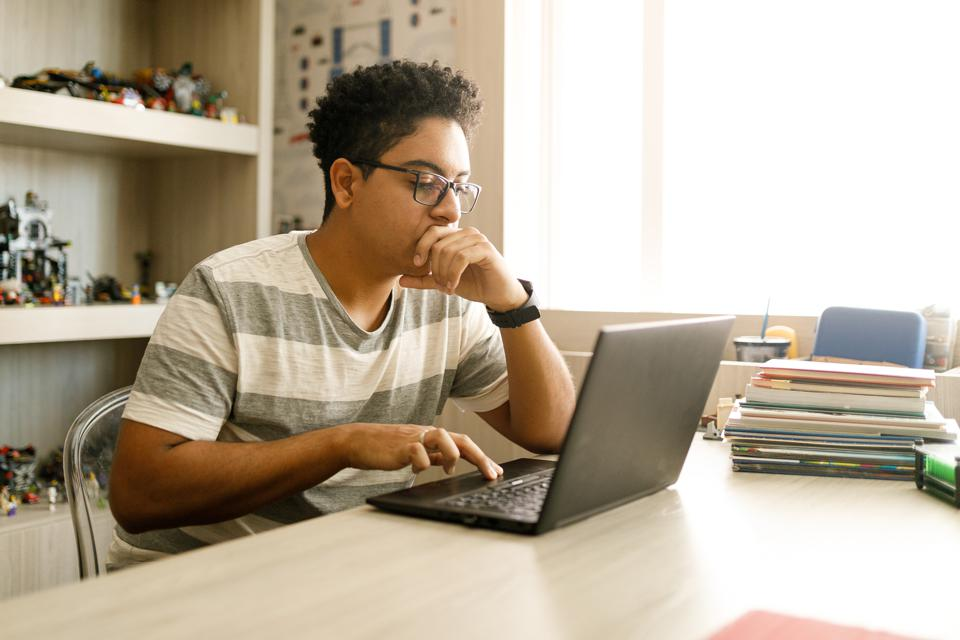 Teenage boy studying with laptop at home