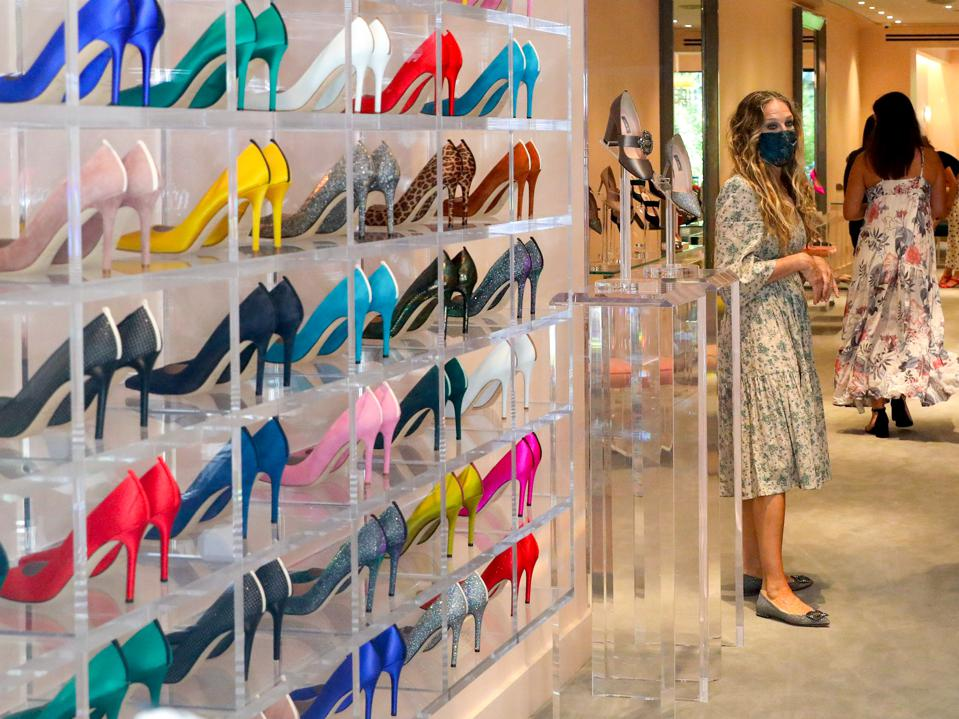 Actress Sarah Jessica Parker stands next a wall of colorful pumps