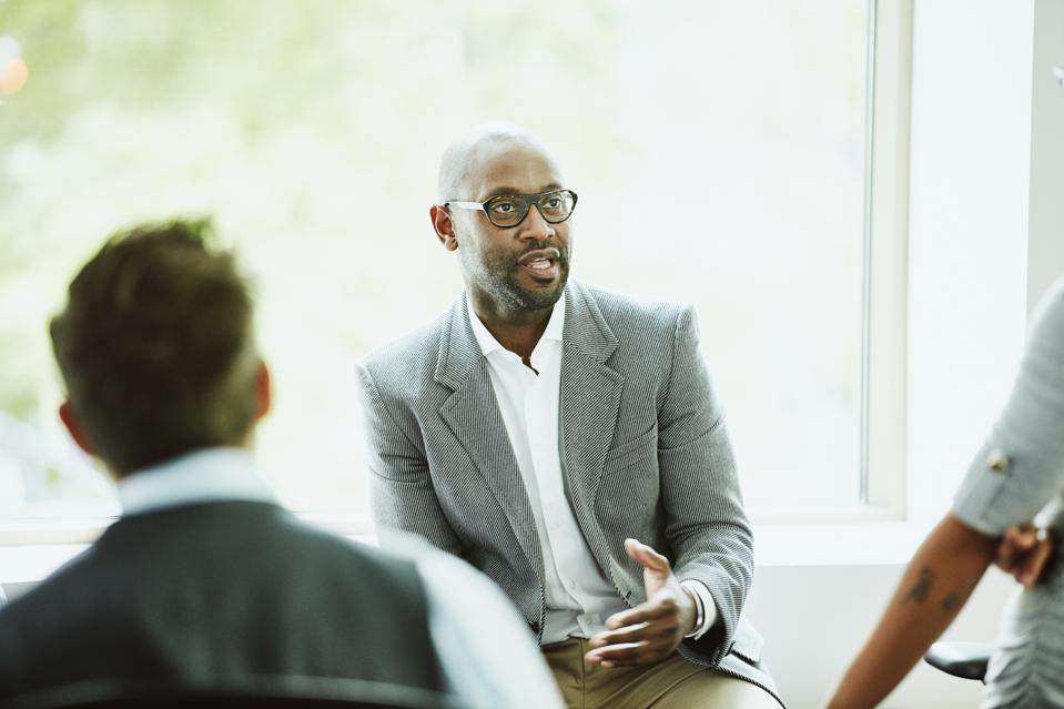 Businessman leading team during informal team meeting in office