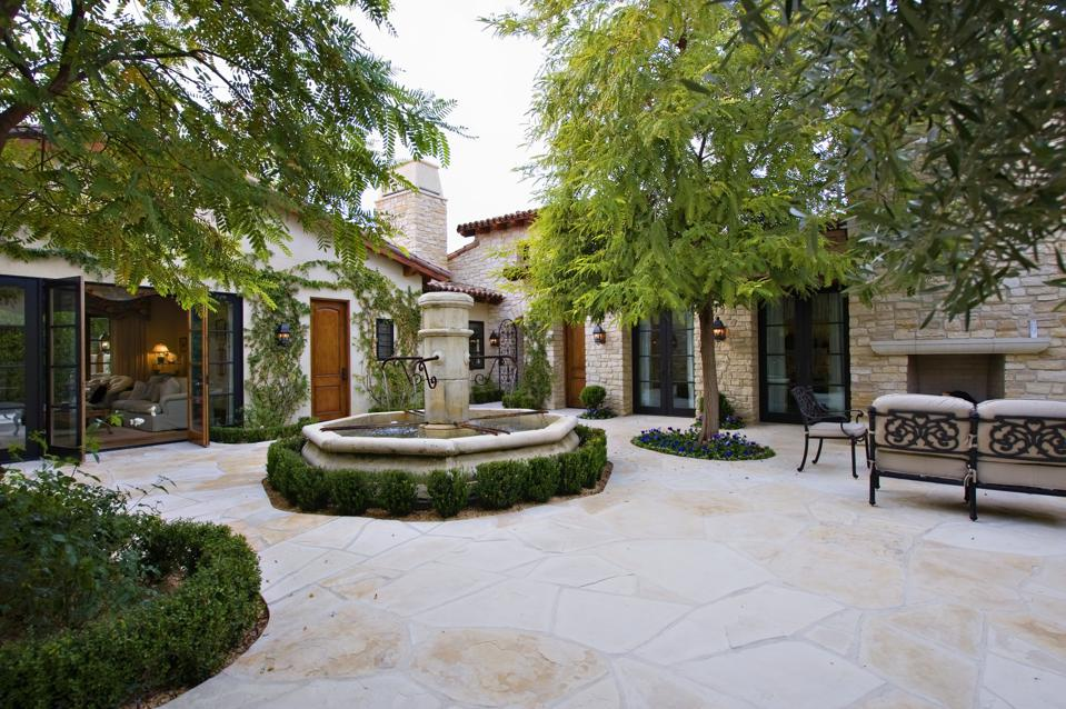 House exterior with a fountain, trees and patio furniture