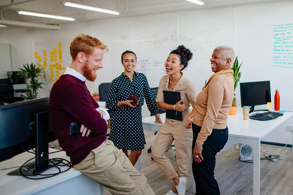 Multi-ethnic group of coworkers laughing together at the office