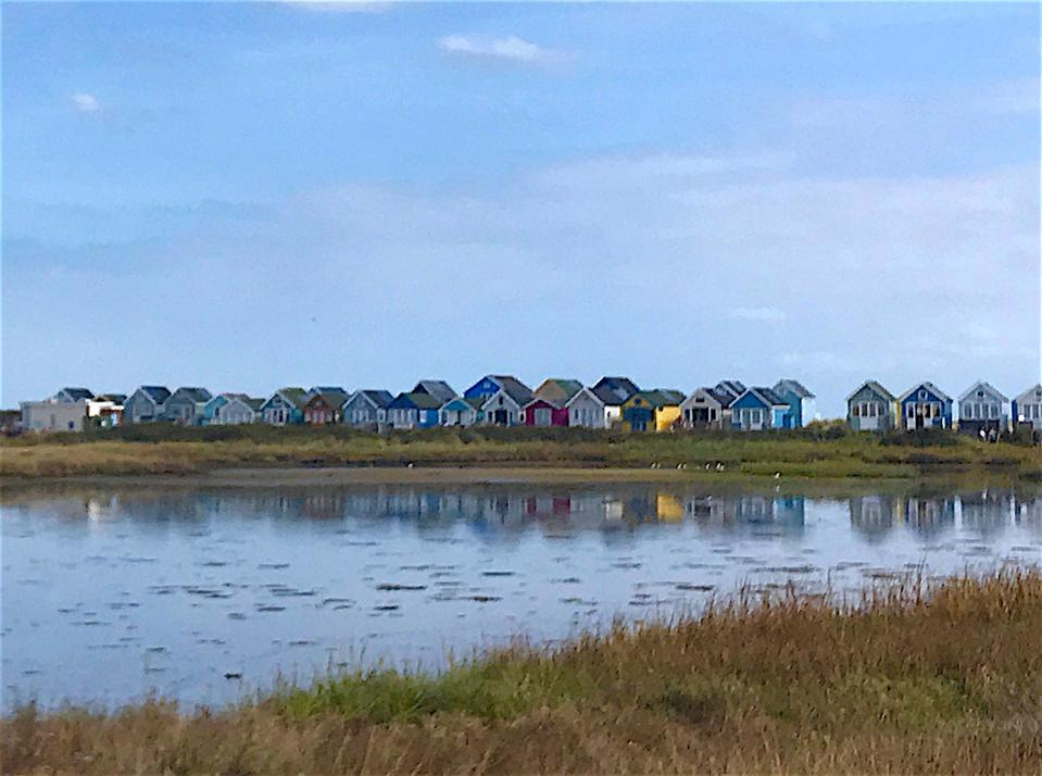 row of colorful beach huts on harbour