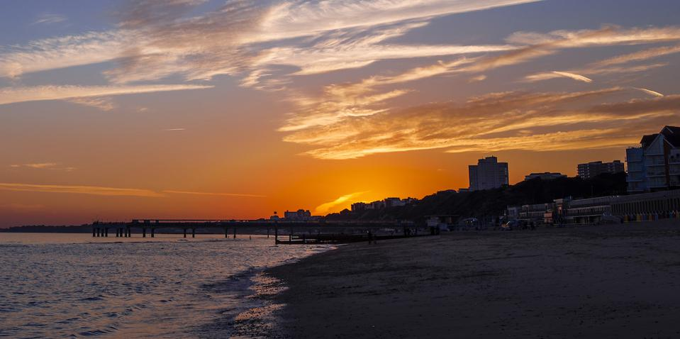 orange sunset, beach and pier and buildings