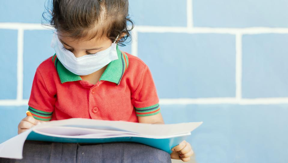 Covid 19 or Coronavirus and Air pollution pm2.5 concept - Little girl wearing medical mask and busy in writing at school - showing Wuhan covid-19 or sars cov 19 outbreak or epidemic of virus.