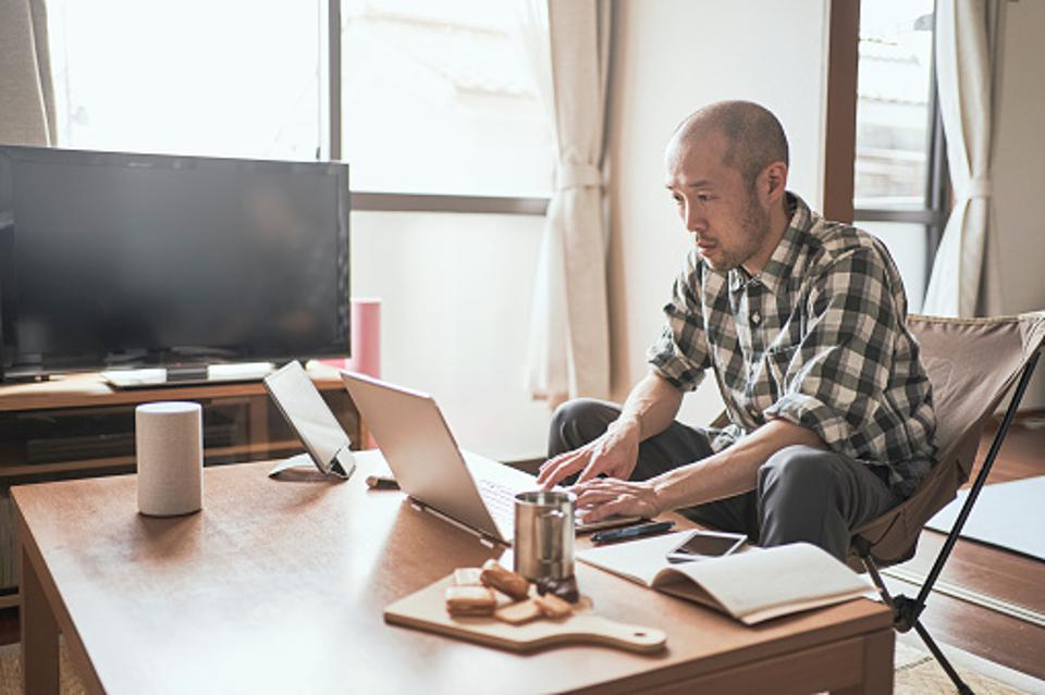Individual using a laptop in a living room