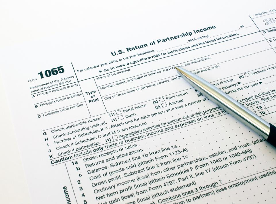 US tax form 1065 with a silver pen