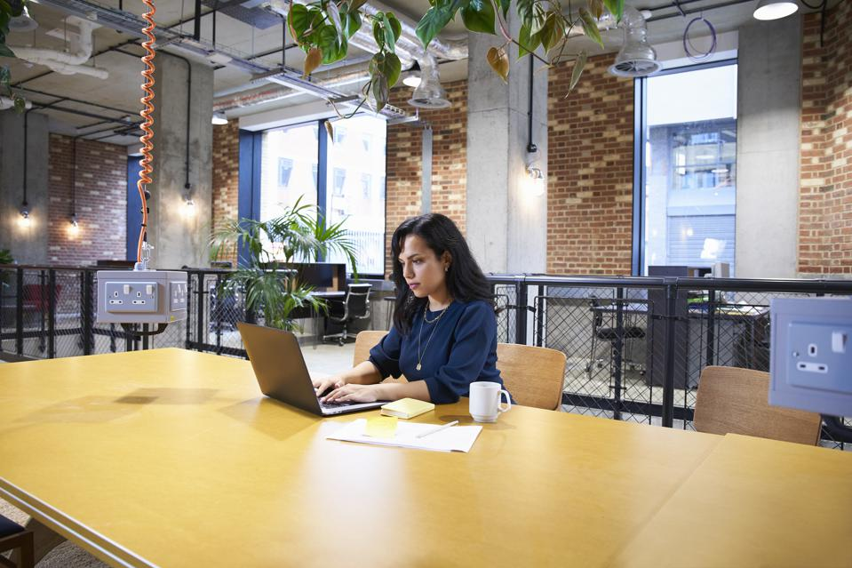 woman in open plan office with laptop