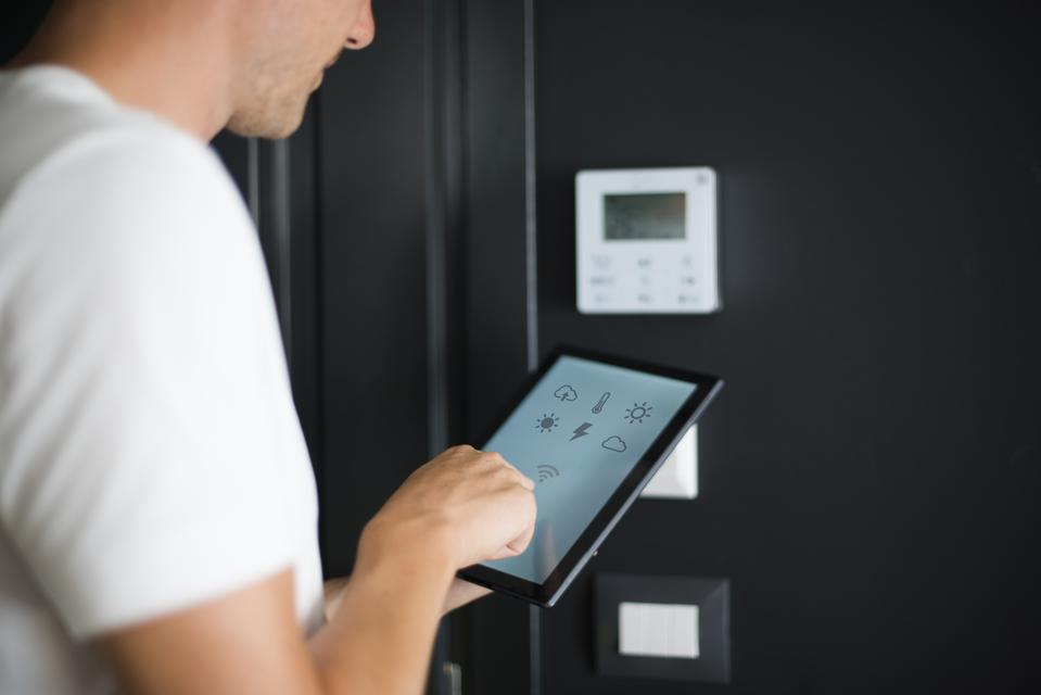 Man using digital tablet with smart home control functions