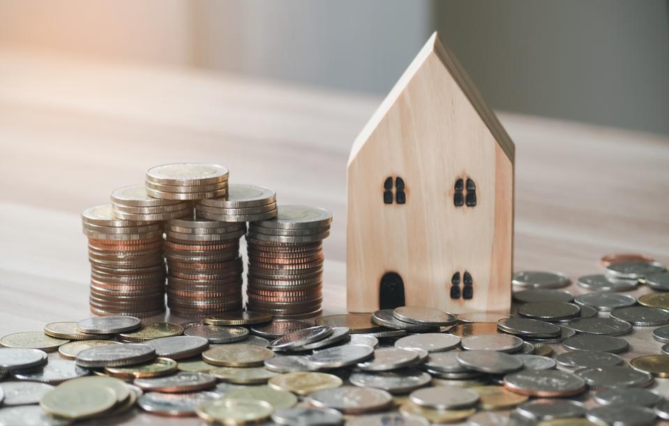 Wood house model with stack of coins on wooden table background. Savings Plans for Housing. Finance and Banking about House concept.