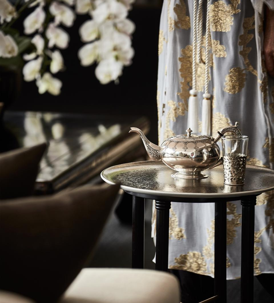 A Moroccan teapot on a table and a woman wearing a lovely Marie France Van Damme caftan.
