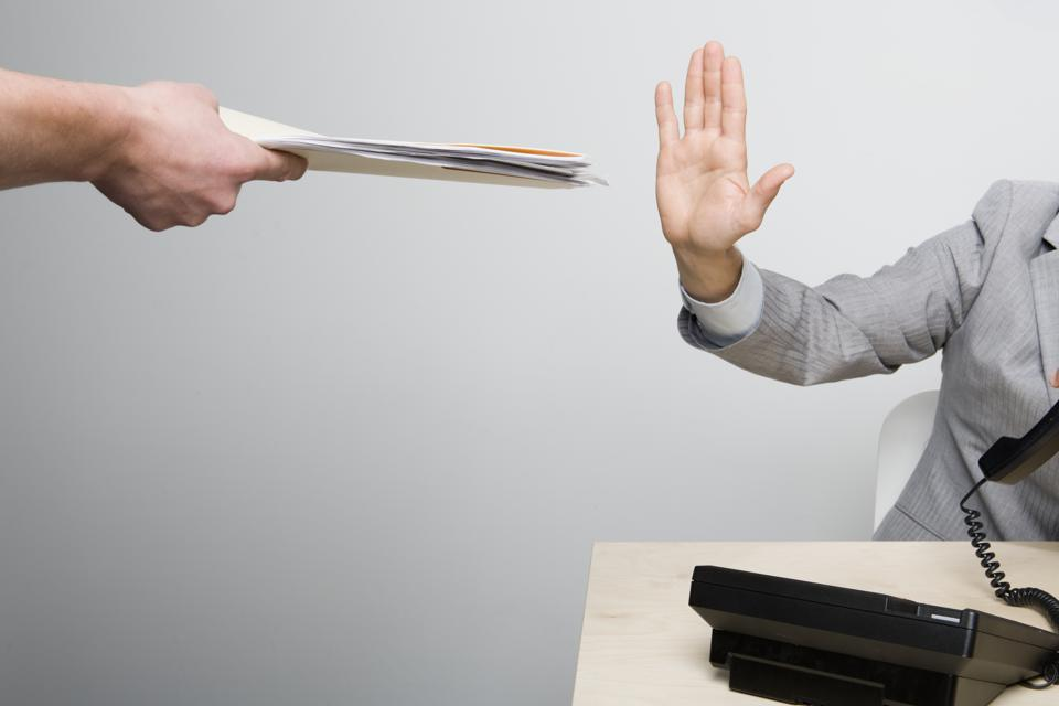 Businessman holding hand up to paperwork