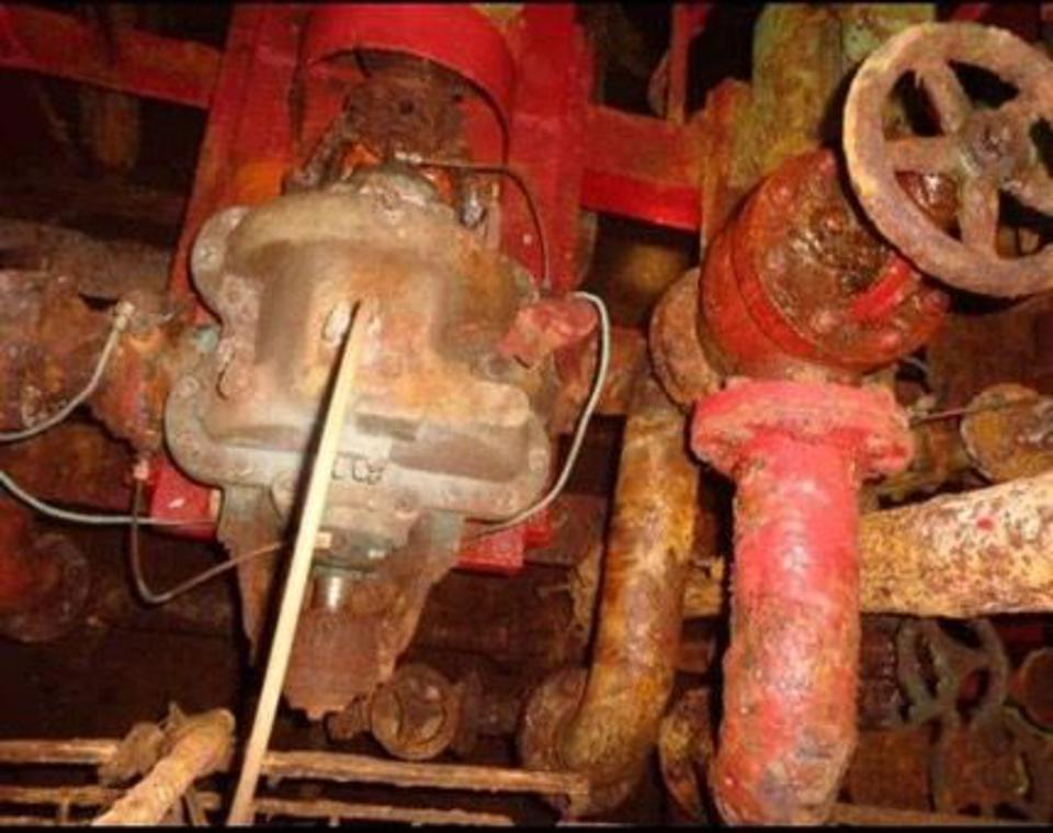 Corroded valves and piping inside an oil tanker.