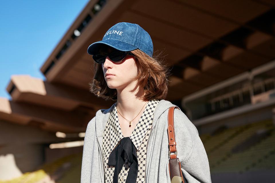 A model wearing sunglasses, denim baseball cap, grey hoodies and bow-neck dress