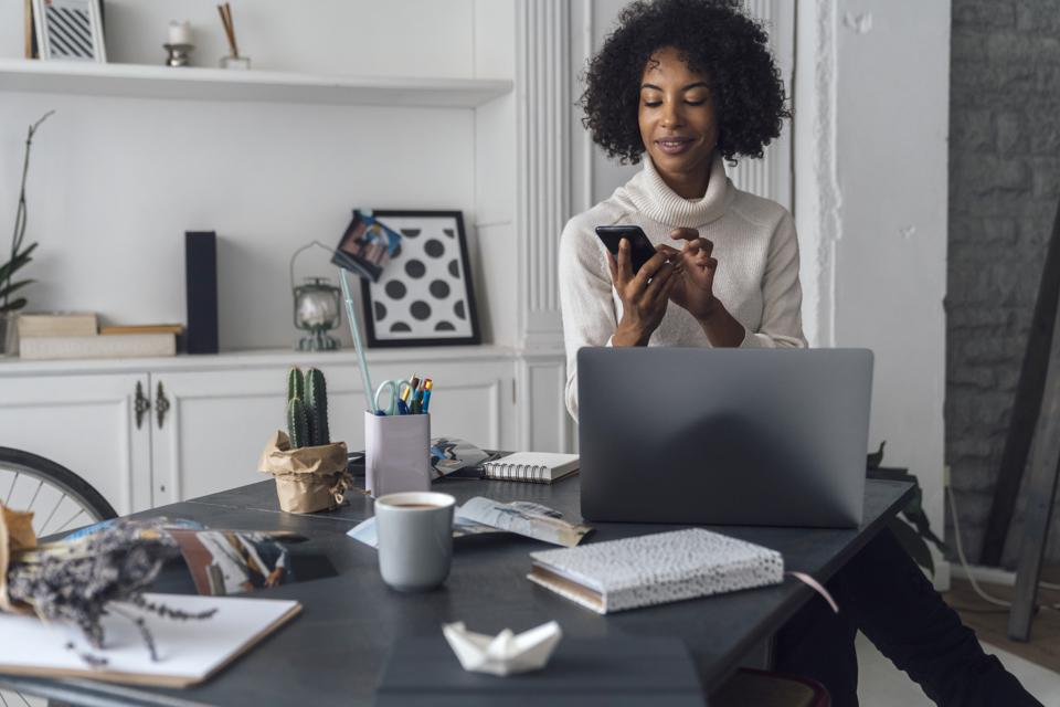 Mid adult woman working in her home office, using smartphone