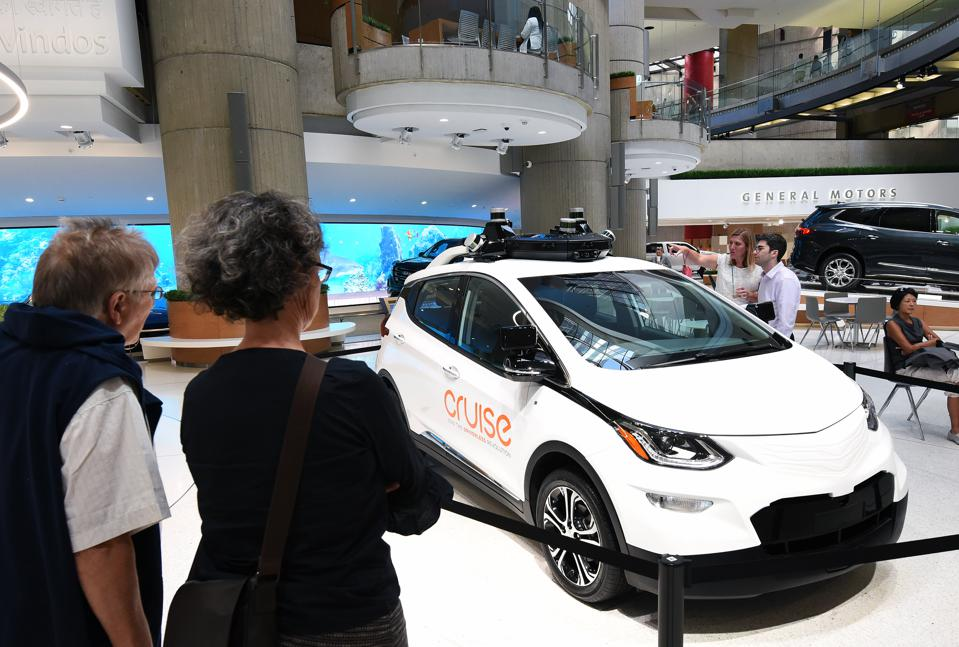 People admire a GM Cruise self-driving car on display at the...