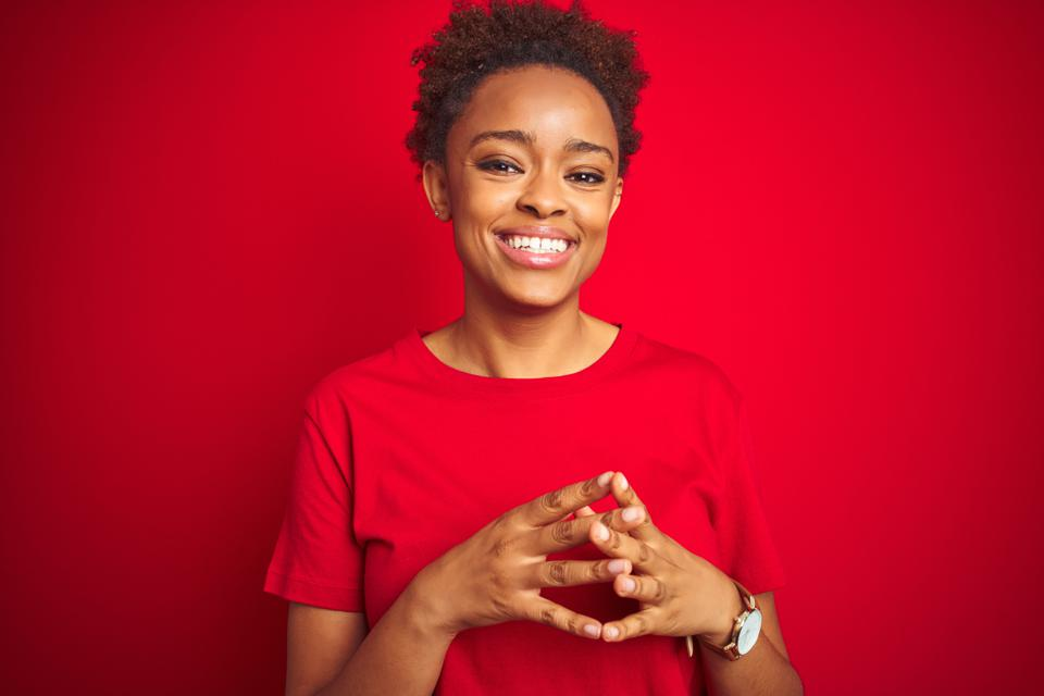 Young beautiful african american woman with afro hair over isolated red background Hands together and fingers crossed smiling relaxed and cheerful. Success and optimistic